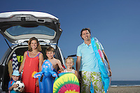 Portrait of family with three children (3-11) at beach by car