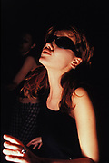 Female dancing in dark club with sunglasses on, Croatia, 1997.