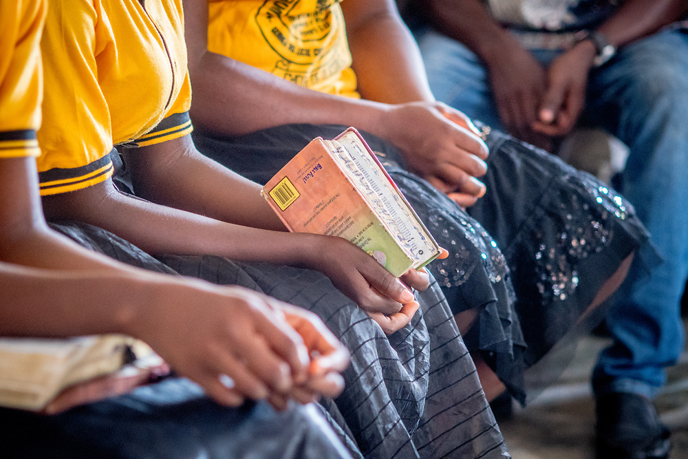 A person cups a bible while sitting in a church service in Ganta,Liberia