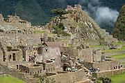 Visitors touring the Inca ruins at Machu Picchu, Peru.