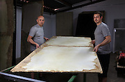 The team brings the wooden sheet with fixed skins into the drying area at the tannery factory of Scriptorium SL in Valencia, Spain. Picture by Manuel Cohen