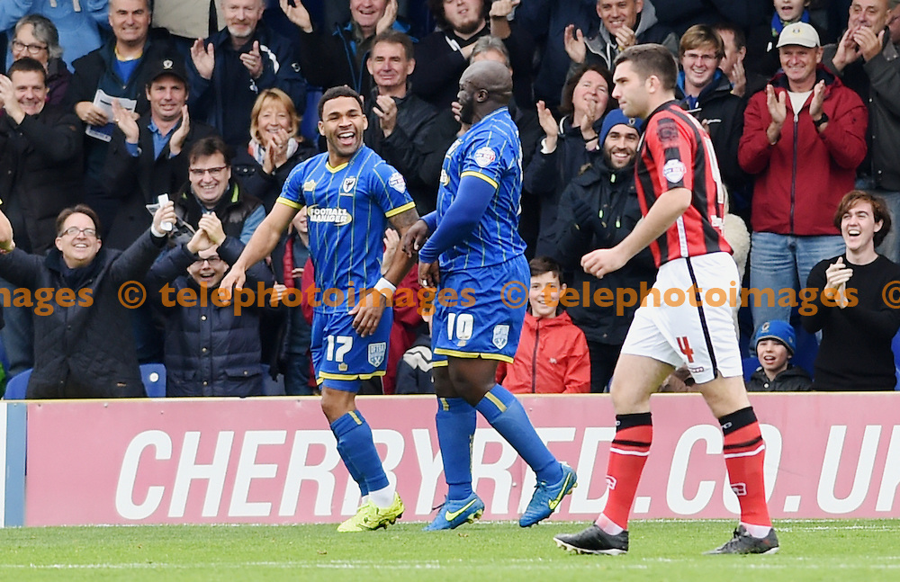 Andy Barcham (left) of Wimbledon celebrates after scoring the opening goal with Bayo Akinfenwa during the Sky Bet League 2 match between AFC Wimbledon and Morecambe at the Cherry Red Records Stadium in Kingston. October 17, 2015.<br /> Simon  Dack / Telephoto Images<br /> +44 7967 642437