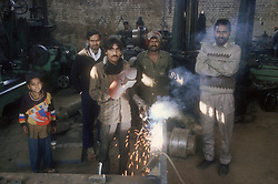 Metal work shop in the Punjab; India; with workers welding,