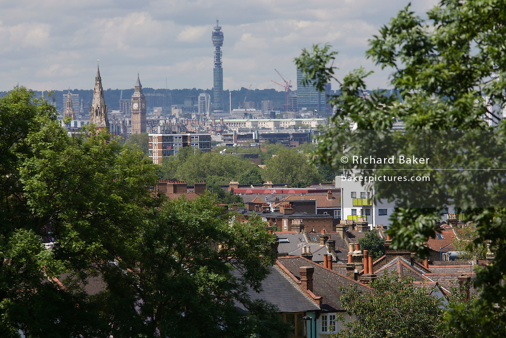The clock tower of the Palace of Westminster housing Big Ben seen over south London residential rooftops.