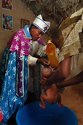 "Tiblits neighbor Zaid Tesheme, 31 has her baby baptized with the name Mihreteab inside Coptic St. Mary's chapel in the village of Fithi which means ""justice"" on the outskirts of  Barentu, Eritrea August 27, 2006. During this ceremony, . The donkey that Tiblets received from the womens union ""Hamade"", helped them prepare for the celebration afterwards.   (Photo by Ami Vitale)"