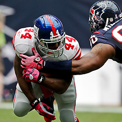 October 10, 2010; Houston, TX USA; New York Giants running back Ahmad Bradshaw (44) is tackled by Houston Texans defensive end Mario Williams (90)during the first half at Reliant Stadium. Mandatory Credit: Derick E. Hingle