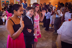 """Students enter the room in a  promenade.  Students of Dancing Classrooms of the Virgin Islands dance at a reception for their parents, family community, and school partners at the Virgin Islands Council on the Arts.  Students spent weeks learning the Tango, Foxtrot, Meringue, Swing, Rumba, and Waltz that will culminate in """"Colors of the Rainbow"""" team match competition at Reichhold Center for the Arts on Saturday, May 9, 2015.  St. Thomas, USVI.  8 May 2015.   © Aisha-Zakiya Boyd"""
