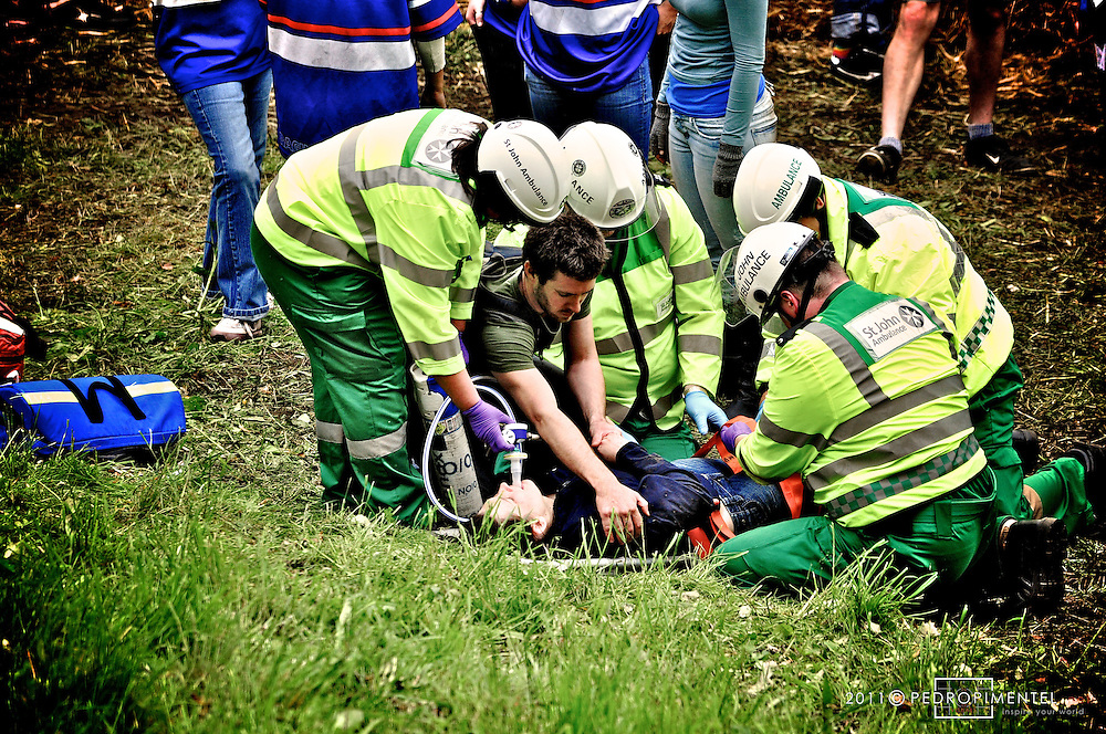 Cheese Rolling Festival. INjured competitor gets imediate assistance by the St John Ambulance during the traditional Gloucestershire Cheese Rolling festival. Cooper's Hill, UK.