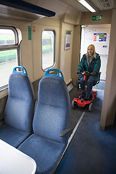 Woman steering electric mobility scooter through a train carriage,
