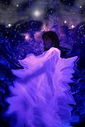 A woman wearing a glowing veil dances amongst the stars.Black light