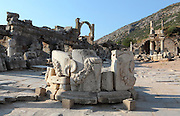 West side of Domitian Square, with the arch of the Fountain of Pollio in the centre distance and the Temple of Domitian on the right, Ephesus, Izmir, Turkey. In the foreground is a large round monument which was moved here in the 4th century AD. It is carved with bull's heads and garlands. Ephesus was an ancient Greek city founded in the 10th century BC, and later a major Roman city, on the Ionian coast near present day Selcuk. Picture by Manuel Cohen