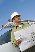 Architect talking on mobile phone holding blueprints