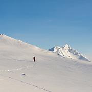 Arnar Felix Einarsson walking on skis on mt. Haki with mt. Hornklofi in the background, Tindfjöll mountain range, Iceland.
