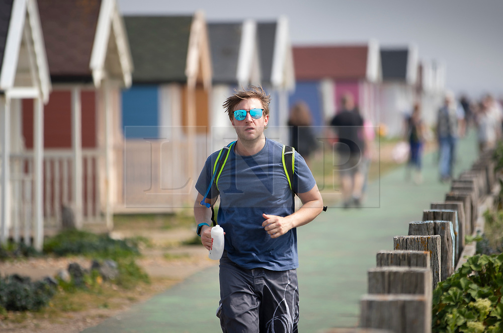 © Licensed to London News Pictures. 22/04/2019. Lancing, UK. A joggers in Lancing in West Sussex runs past coloured beach huts on the sea front as most of the UK enjoys record breaking high temperatures over the Easter weekend. Photo credit: Peter Macdiarmid/LNP