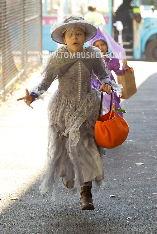 Middletown, New York  - Girls wearing costumes run to the Halloween Fall Festival at the Middletown YMCA's Center for Youth Programs on Oct. 25, 2014.
