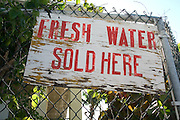 Sign offering fresh water for sale along the King's Highway in Alice Town on the tiny Caribbean island of Bimini, Bahamas