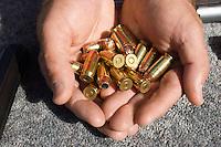 Mans hands holding bullets, close-up