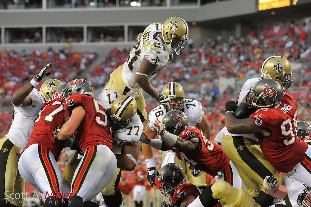 Nov. 22, 2009; Tampa, FL, USA; New Orleans Saints running back Mike Bell (21) leaps over the line for a touchdown during the Saints 38-7 win over the Tampa Bay Buccaneers at Raymond James Stadium. ©2009 Scott A. Miller.© 2009 Scott A. Miller