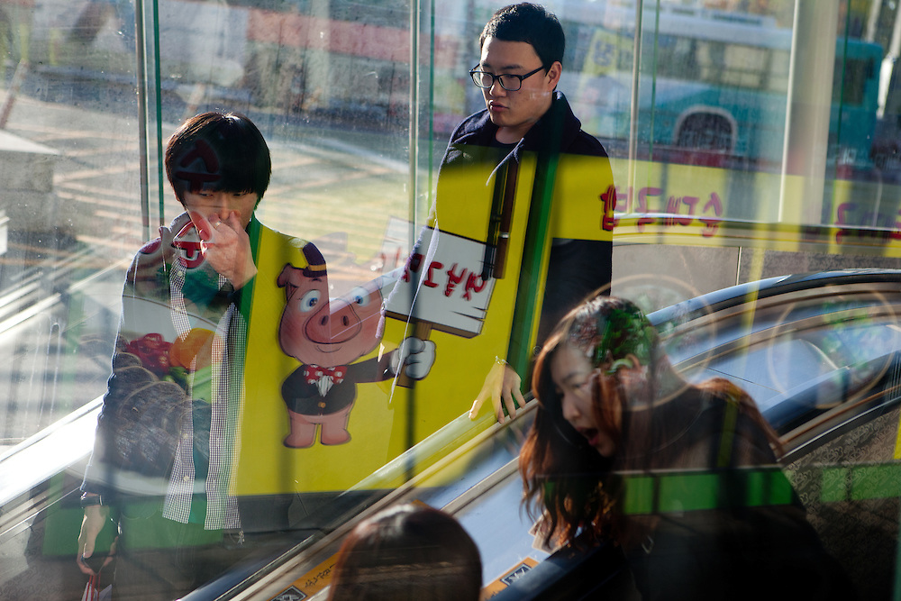 Daegu/South Korea, Republic Korea, KOR, 03.11.2010: People entering a subway station in the South Korean city of Daegu. The logo of a butcher reflected in the glass eindow.