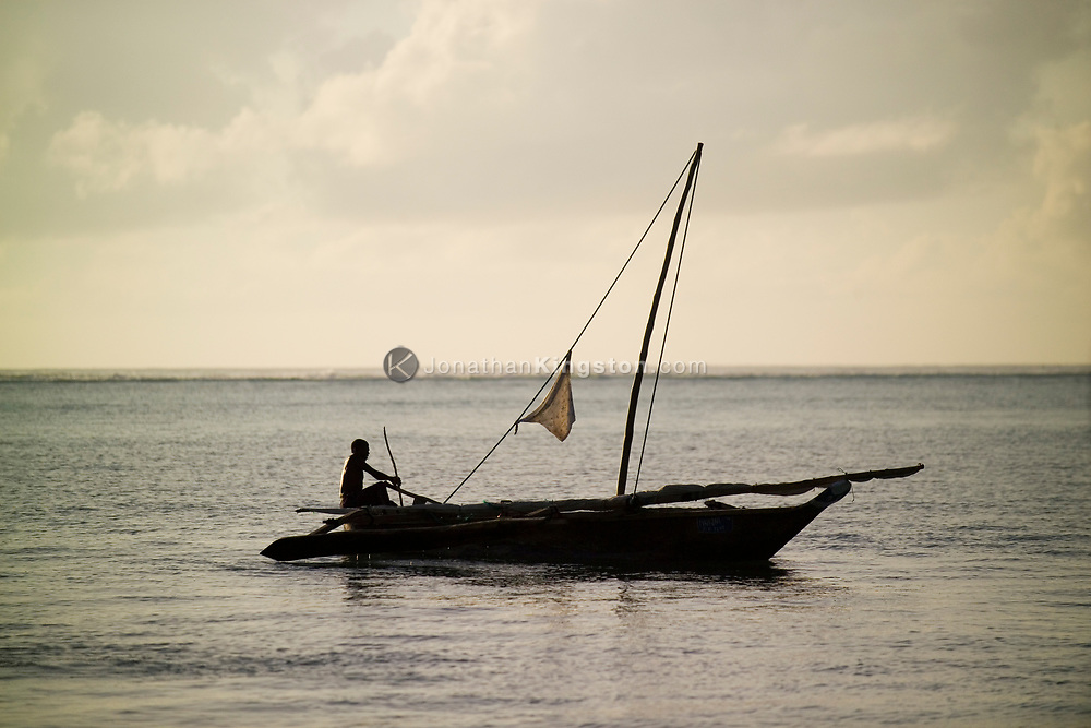 A fisherman prepares his dhow, a carved wooden boat, off the shores of the beach in Matemwe, Zanzibar, Tanzania.