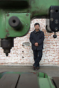 Chinese artist and curator of Factory 798 Xu Yong in his gallery in Beijing in front of a leftover machine.