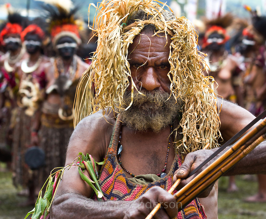 Portrait of an old man poised with a bow and arrow. He is dressed in traditional tribal dress for the Goroka Show, an annual Singsing Festival in the highlands of Papua New Guinea