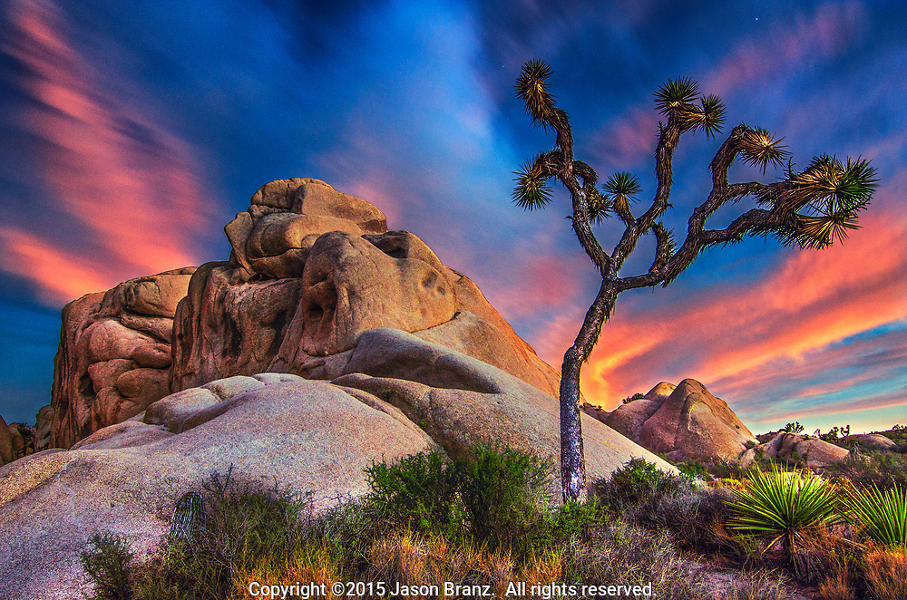 Long exposure of twilight light on clouds over a rock formation, Joshua Tree National Park, California.