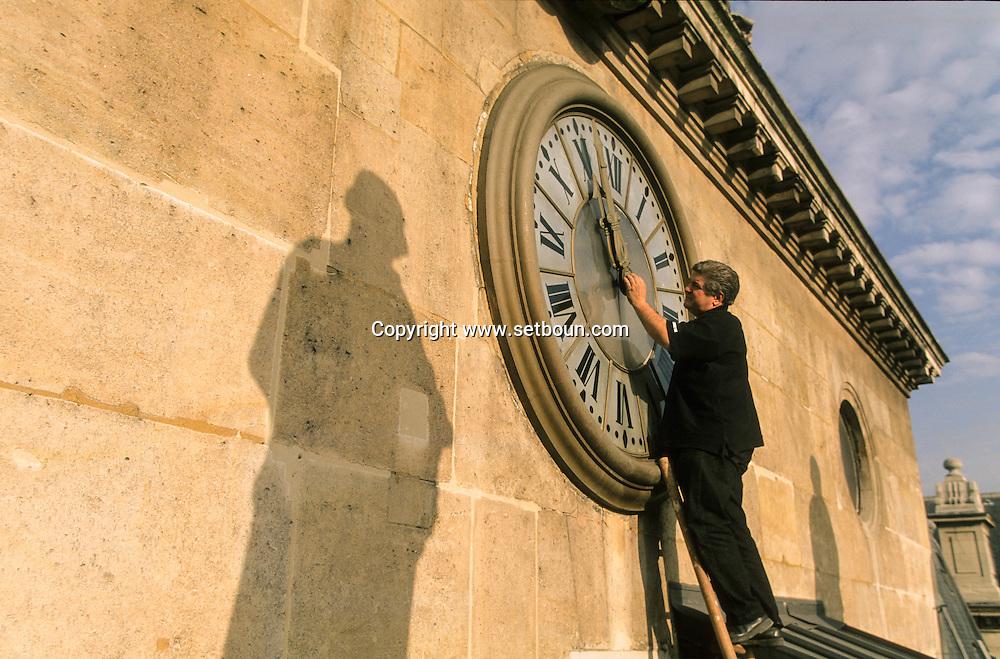 France. Paris. Man Adjusting Clock at Palais de Justice .  the giant clock of  the palais de justice facade