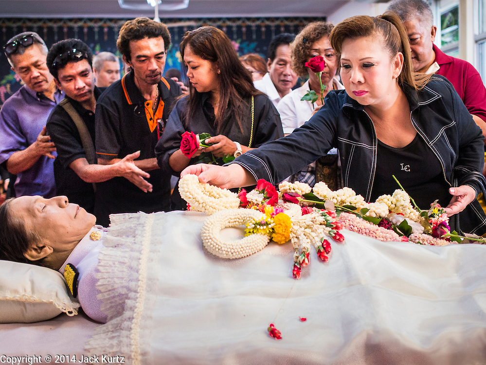 12 OCTOBER 2104 - BANG BUA THONG, NONTHABURI, THAILAND: People lay flower garlands on the body of  Apiwan Wiriyachai during the first day of his funeral rites at Wat Bang Phai in Bang Bua Thong, a Bangkok suburb, Sunday. Apiwan was a prominent Red Shirt leader, member of the Pheu Thai Party of former Prime Minister Yingluck Shinawatra, and a member of the Thai parliament. The military government that deposed the elected government in May, 2014, charged Apiwan with Lese Majeste for allegedly insulting the Thai Monarchy. Rather than face the charges, Apiwan fled Thailand to the Philippines. He died of a lung infection in the Philippines on Oct. 6. The military government gave his family permission to bring him back to Thailand for the funeral. He will be cremated later in October. The first day of the funeral rites Sunday drew tens of thousands of Red Shirts and their supporters, in the first Red Shirt gathering since the coup.    PHOTO BY JACK KURTZ