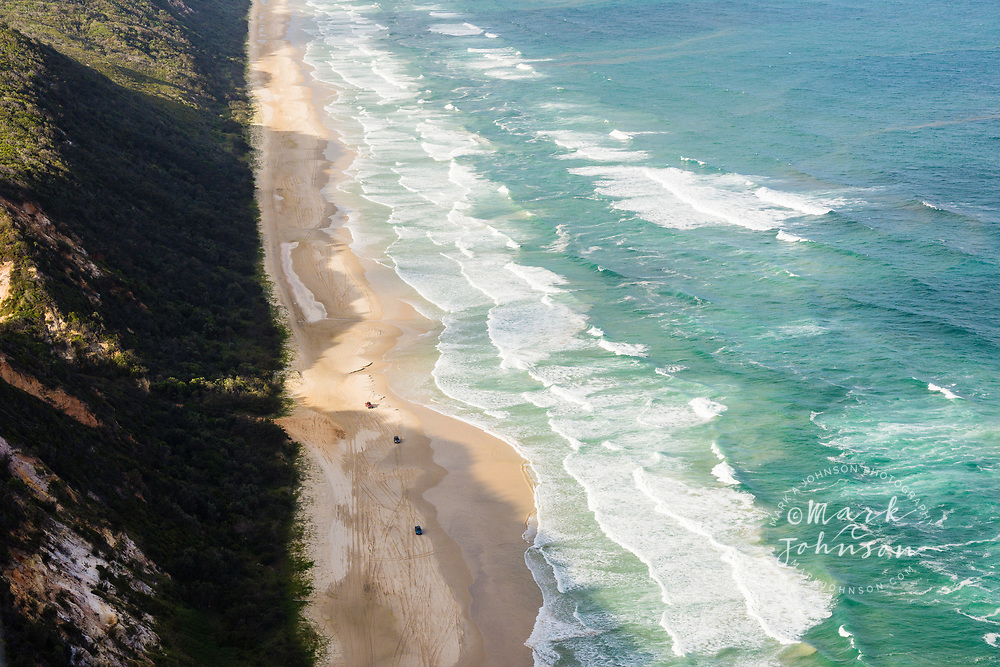 Aerial photograph of 4 wheel drive trucks driving on the beach, Great Sandy National Park, Sunshine Coast, Queensland, Australia