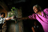 A woman is handed some plants in her home in El Ofrio, a small remote village in the southern Colombian state of Nariño, on Saturday, June 23, 2007. There are coca fields located in the vicinity of El Ofrio, but the residents know that soon fumigation and manual eradication of their coca crops by the Colombian government will force them to find a new means to earn cash. (Photo/Scott Dalton)