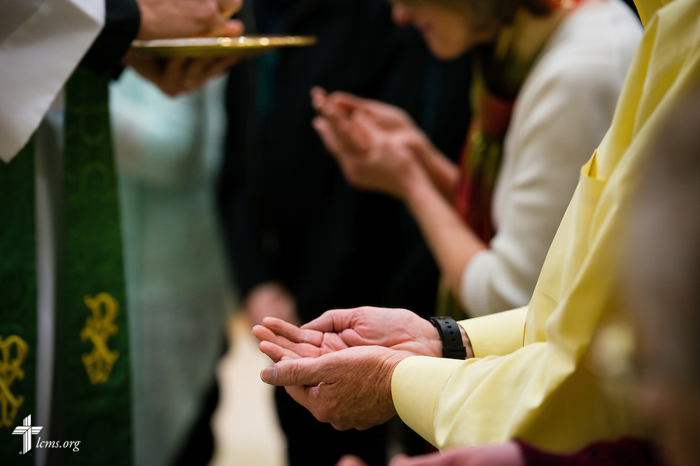Parishioners extend their hands for the distribution of the Sacrament at Divine Service on Sunday, Nov. 23, 2014, at Living Faith Lutheran Church in Cumming, Ga. LCMS Communications/Erik M. Lunsford