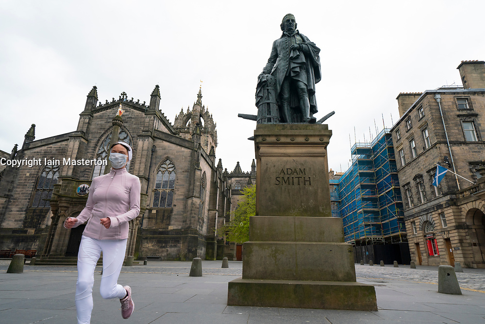 Edinburgh, Scotland, UK. 29 April 2020. Views of Edinburgh Old Town as coronavirus lockdown continues in Scotland. Streets remain deserted and shops and restaurants closed and many boarded up. Scottish Government now recommends public to wear face masks. Female jogger wearing face mask runs along a deserted Royal Mile past statue of Adam Smith. Iain Masterton/Alamy Live News