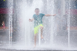 © Licensed to London News Pictures. 24/07/2018. Bradford UK. 12 year old Roman Kincaid cools of in the water fountains at Centenary Square in Bradford as the UK heatwave continues. The public are being advised to take shelter from the sun, as the joint warning from the NHS, Public Health England and the Met Office says there is a 90% probability of heatwave conditions until 09:00 BST on Friday. Photo credit: Andrew McCaren/LNP