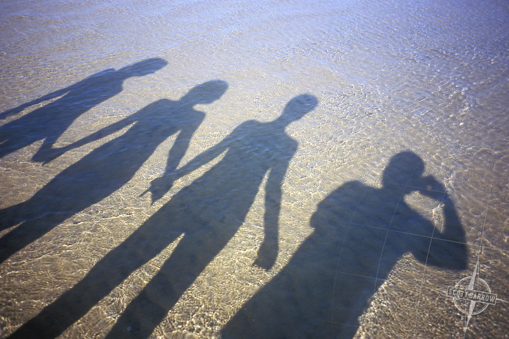 shadows of mother and daughters holding hands on beach, with selfportrait of photographers shadow.