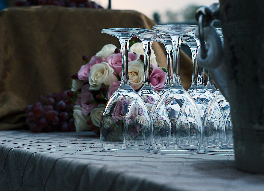 Wine glasses, full of reflection, rest upside down on table top among white and pink roses, grapes and ice-bucket.