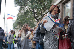 © licensed to London News Pictures. London, UK 06/05/2012. A woman reads a leaflet about French National Front Party as French nationals queueing outside the French Embassy in London to vote the second round of Presidential Elections, this noon (06/05/12). Photo credit: Tolga Akmen/LNP