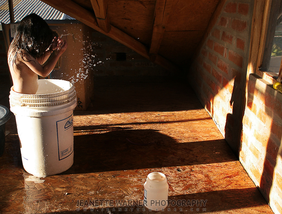 Micaela takes a bucket bath in the attic in Tabacundo, Ecuador.  Her and her sister are bathing in the attic to stay warmer and get rid of the colds they have started to get.