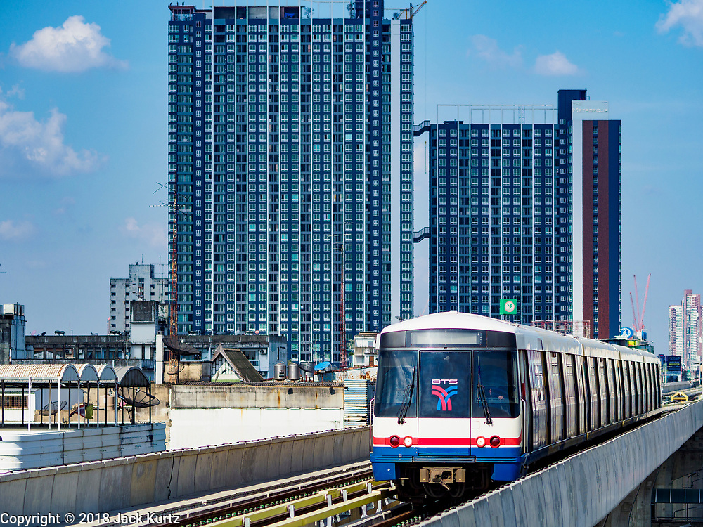 06 DECEMBER 2018 - SAMUT PRAKAN, THAILAND:  A BTS Skytrain goes past new condominiums on the newly opened expansion of the line. The 12.6 kilometer (7.8 miles) east extension of the Sukhumvit Line of the Bangkok BTS Skytrain goes into Samut Prakan, a town east of Bangkok.  The system is now 51 kilometers long (32 miles), including the 12.6 kilometer extension that opened December 06. About 900,000 people per day use the BTS.      PHOTO BY JACK KURTZ
