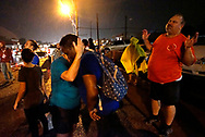 A white woman holds a black woman as they pray during a rain storm at the site of last year's riots on the one year anniversary of the killing of Michael Brown Jr. in Ferguson, Missouri August 9, 2015.  Several hundred people gathered in Ferguson, Missouri, on Sunday to mark the one-year anniversary of the shooting death of an unarmed black teenager by a white police officer that sparked protests and a national debate on race and justice.  REUTERS/Rick Wilking