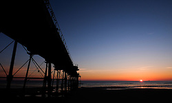 © Licensed to London News Pictures.12/06/15<br /> Saltburn by the Sea, England<br /> <br /> The sun creeps slowly over the horizon as dawn breaks over Saltburn by the Sea.<br /> <br /> Photo credit : Ian Forsyth/LNP