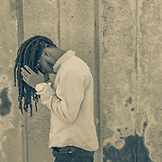 A 17-year-old African American teenager with dreadlocks stands  against a rusting, metal wall, head bent forward, in a junkyard in Rocky Mount, NC.