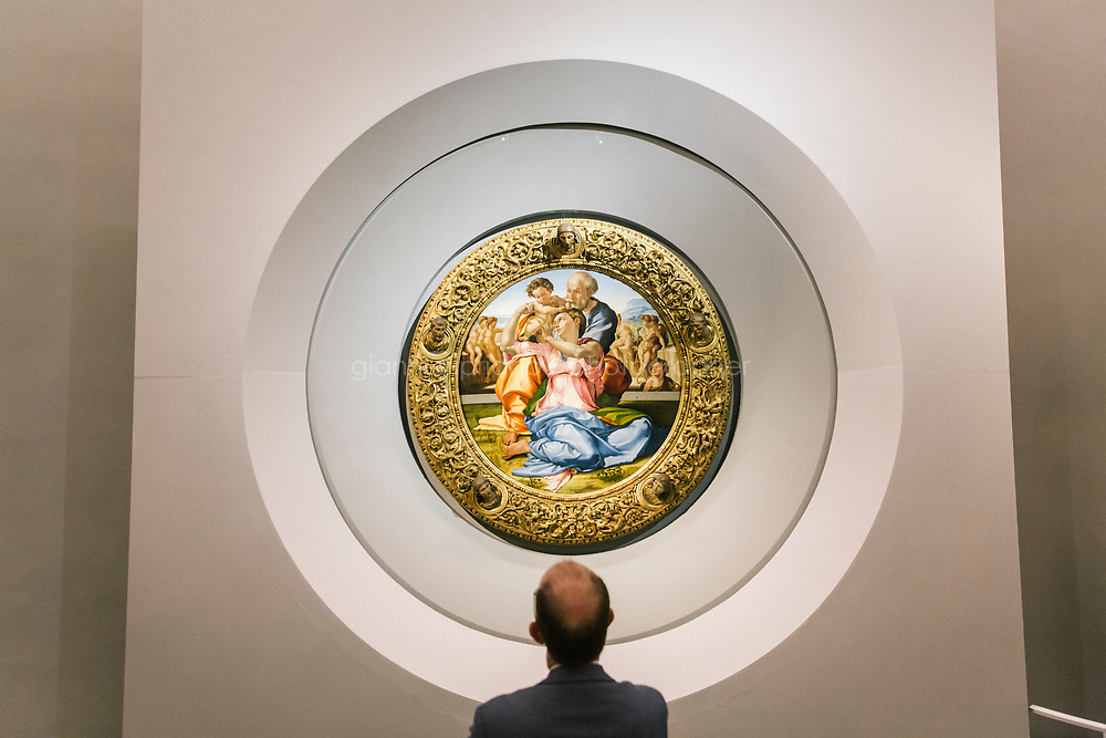 FLORENCE, ITALY - 3 JUNE 2018: A visitor looks at the &ldquo;Holy Family&rdquo;, also known as the Doni Tondo, that Michelangelo painted for the Doni couple around 1503-1504,  here in its new location in room 41at the Uffizi, in Florence, Italy, on June 3rd 2018.<br /> <br /> As of Monday June 4th 2018, Room 41 or the &ldquo;Raphael and Michelangelo room&rdquo; of the Uffizi is part of the rearrangement of the museum's collection that has<br /> been defining Uffizi Director Eike Schmidt&rsquo;s grander vision for the Florentine museum.<br /> Next month, the museum&rsquo;s Leonardo three paintings will be installed in a<br /> nearby room. Together, these artists capture &ldquo;a magic moment in the<br /> first decade of the 16th century when Florence was the cultural and<br /> artistic center of the world,&rdquo; Mr. Schmidt said. Room 41 hosts, among other paintings, the dual portraits of Agnolo Doni and his wife Maddalena Strozzi painted by Raphael round 1504-1505, and the &ldquo;Holy Family&rdquo;, that Michelangelo painted for the Doni couple a year later, known as the<br /> Doni Tondo.