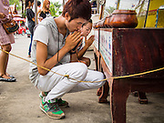 """21 JULY 2013 - BANGKOK, THAILAND:   A man and woman pray at Wat Mahabut on the first day of Vassa, the three-month annual retreat observed by Theravada monks and nuns. On the first day of Vassa (or Buddhist Lent) many Buddhists visit their temples to """"make merit."""" During Vassa, monks and nuns remain inside monasteries and temple grounds, devoting their time to intensive meditation and study. Laypeople support the monastic sangha by bringing food, candles and other offerings to temples. Laypeople also often observe Vassa by giving up something, such as smoking or eating meat. For this reason, westerners sometimes call Vassa the """"Buddhist Lent.""""       PHOTO BY JACK KURTZ"""