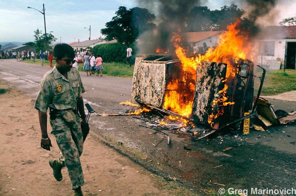 KwaZulu Natal. South Africa. 1994. SADF soldiers passes a burning car in KwaMashu, KwaZuluNatal 1994.