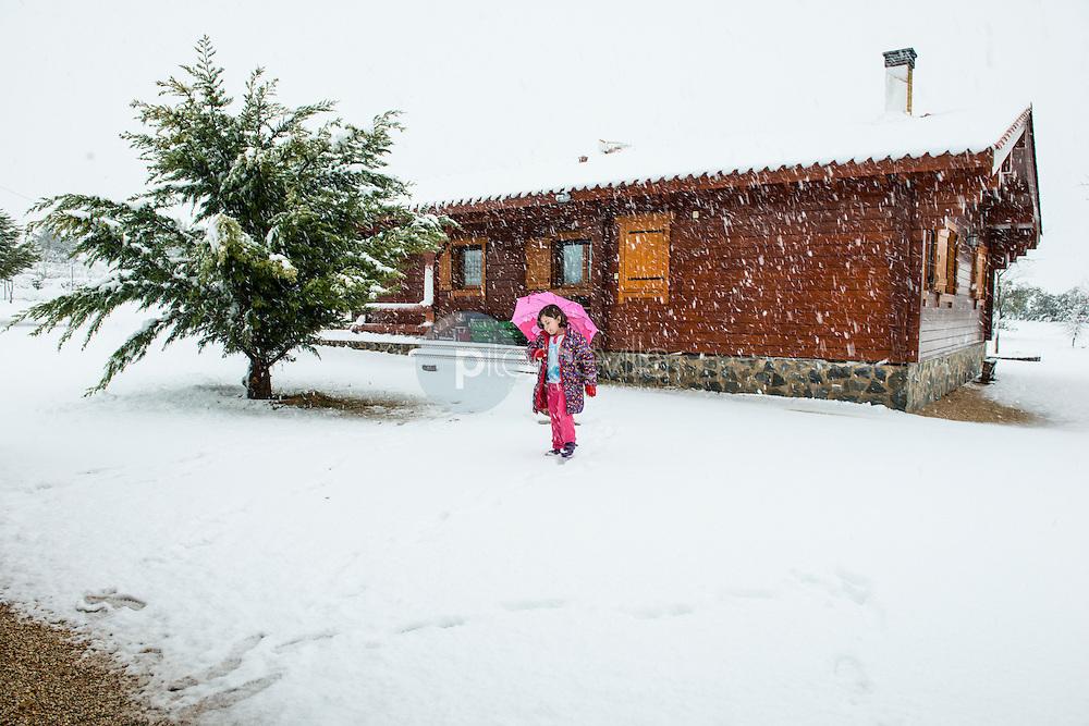 Casa de madera nevada y niña con paraguas. Almansa. Albacete ©Antonio Real Hurtado / PILAR REVILLA