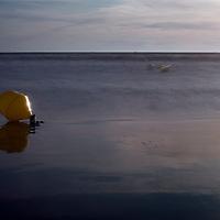 Buoy on the beach. Long exposure shot.