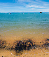 Bright blue water mixes with bright orange sand at Kaiteriteri Beach, on the North shore of New Zealand's South island. This region of New Zealand is also regarding as an entry point to the world . famous Abel Tasman national park.