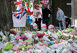 A woman lays flowers at the scene of the Lee Rigby murder in Woolwich in South East London, Monday, 27th May 2013 Picture by :  Stephen Lock / i-Images