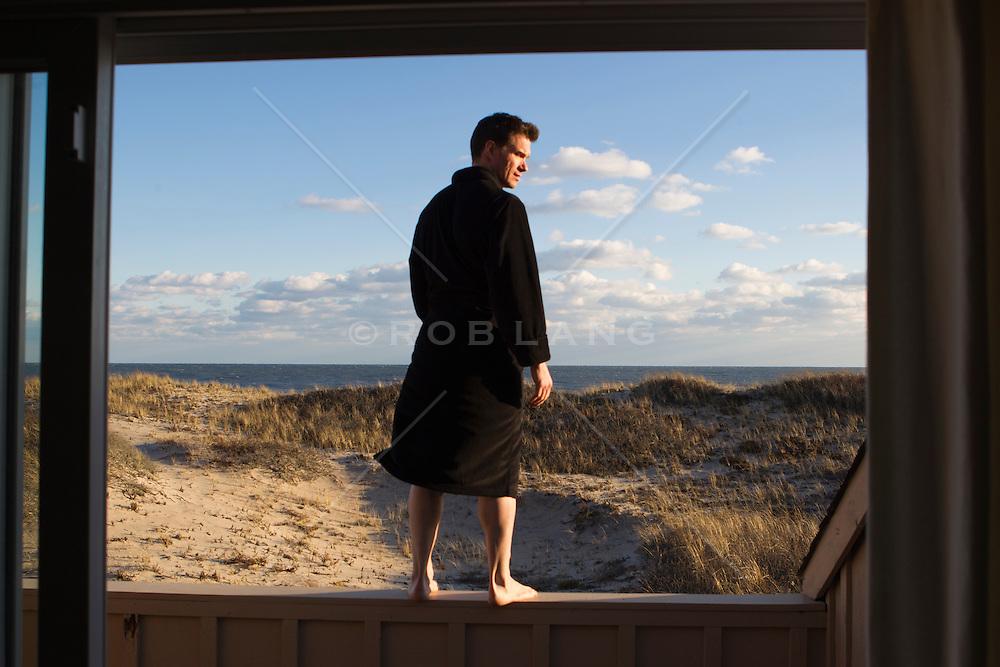 man in a bathrobe on a terrace ledge in Amagansett, NY